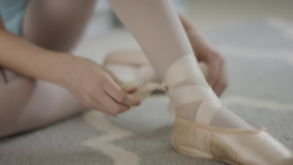 Close Up Shot Of Girl Sitting On Floor Tying Ballet Shoe Stock