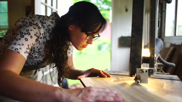 Medium shot of a woman cutting out a piece of wood with a tool Royalty-free stock video
