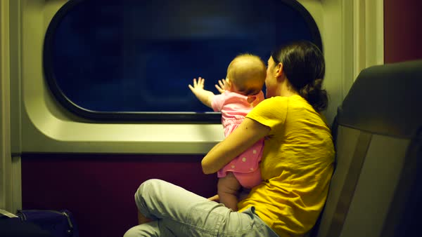 Hand-held medium shot of mother and baby traveling by train Royalty-free stock video
