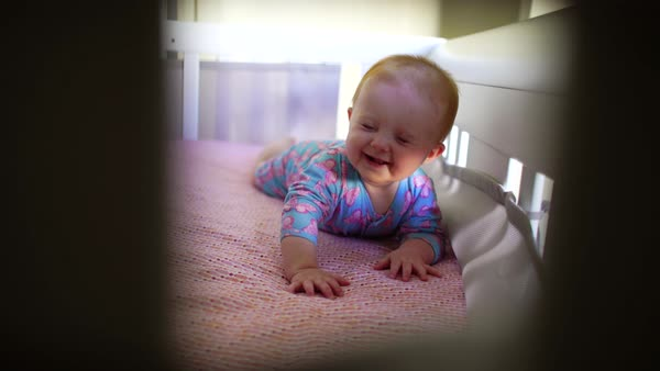Hand-held shot of a baby smiling in a crib Royalty-free stock video