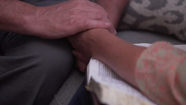 Hand-held shot of two people holding hands over The Bible Royalty-free stock video