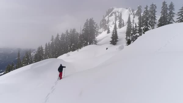Aerial of Man Snowshoeing to Summit on Mountain Ridge with Fresh Deep Powder Royalty-free stock video