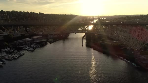 Aerial Dolly of Cars Commuting Across Water Canal on Big City Bridge at Sunset Royalty-free stock video