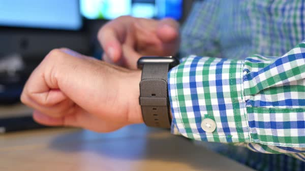 A businessman uses a smartwatch at his desk to schedule an appointment.  	 Royalty-free stock video