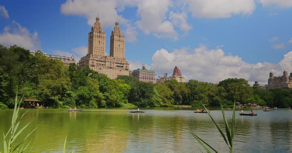 NEW YORK - Circa July, 2016 - A day establishing shot of people in rowboats on the Lake in Central Park with upscale apartment buildings in the distance.  	 Royalty-free stock video
