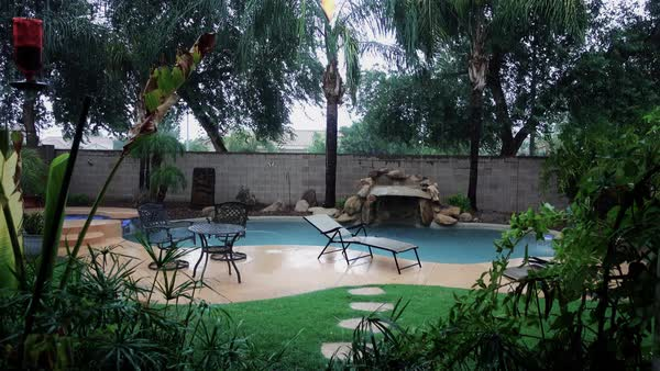 A daytime establishing shot of a backyard pool in a rain storm.  	 Royalty-free stock video