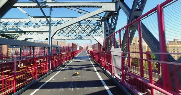 A personal perspective view walking or riding on the pedestrian sidewalk portion of the Williamsburg Bridge over the East River between Manhattan and Brooklyn. Royalty-free stock video