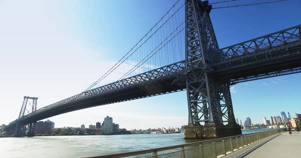 A daytime establishing shot of the Williamsburg Bridge over the East River between Manhattan and Brooklyn.  	 Royalty-free stock video