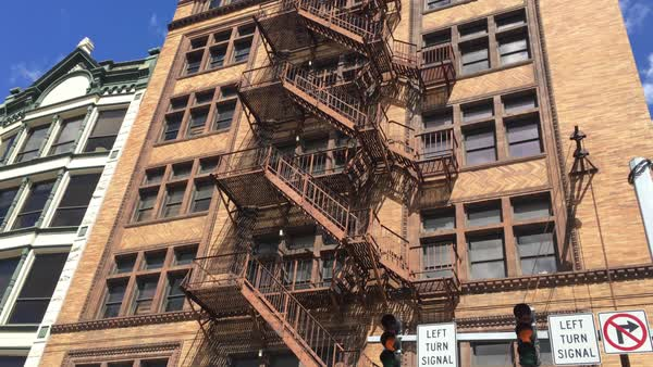 A daytime establishing shot of an apartment or office building with a fire escape on the front.  	 Royalty-free stock video
