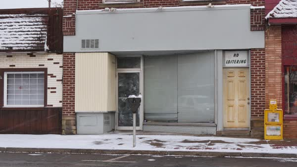 A wintry establishing shot of an empty, abandoned storefront in a small town Royalty-free stock video