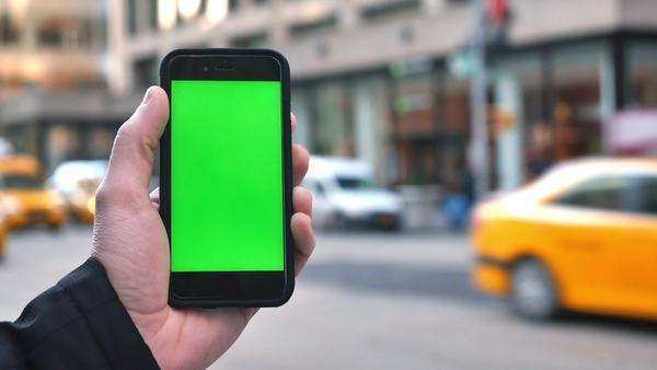 A man holds up a green screen smartphone against Manhattan's busy, 5th Avenue traffic. Royalty-free stock video
