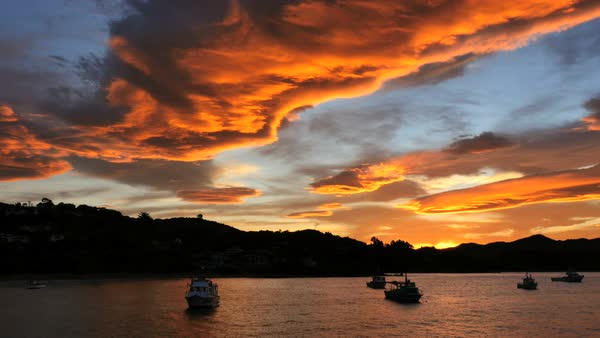 A beautiful orange cloud hovers above boats in a bay after sunset. Royalty-free stock video