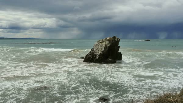 Rain falls offshore in a view of a rock with waves splashing around it. Royalty-free stock video