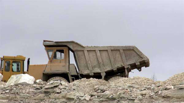 A yellow truck on standby in a limestone mining industry stock footage