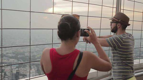 Handheld shot of tourists taking pictures at an observation deck in Bangkok, Thailand Royalty-free stock video