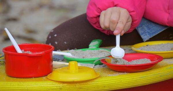Little girl plays with toy dishes in the yard. girl's hands with plastic white spoon, girl puts sand in toy cookware. Royalty-free stock video