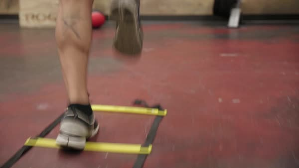 Hand-held shot of a man exercising with a speed ladder Royalty-free stock video
