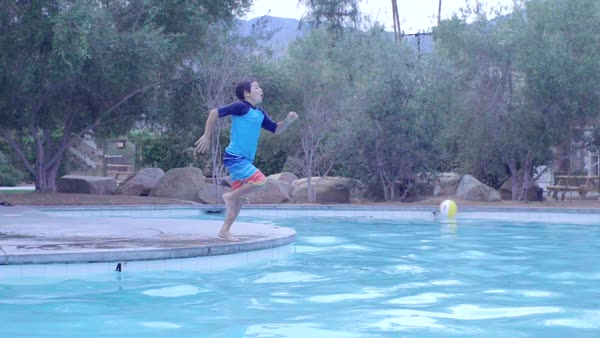 Young boy running and jumping into the pool. Royalty-free stock video