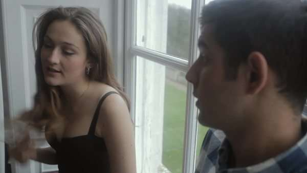 Medium close-up shot of a young couple talking by the window Royalty-free stock video