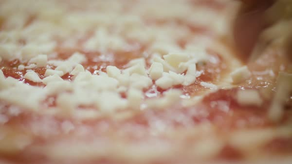 Hand-held shot of person sprinkling cheese on a pizza Royalty-free stock video