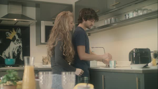 Hand-held shot of a young couple making a tea in a kitchen Royalty-free stock video