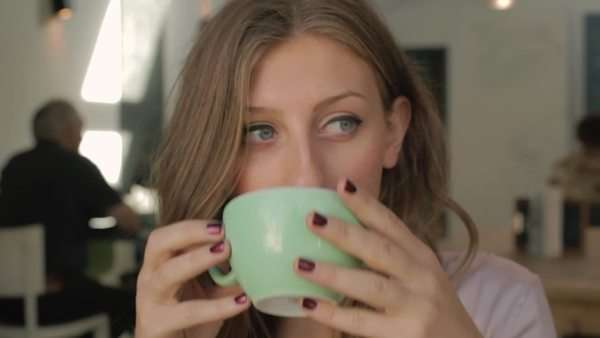 Medium close-up shot of a woman drinking coffee in a coffee shop Royalty-free stock video