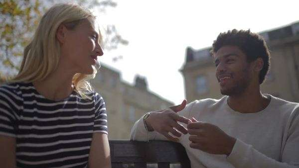 Medium shot of a young couple talking on a bench Royalty-free stock video