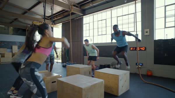 Instructor clapping his hands in encouragement while fit strong healthy people do box jumps in crossfit gym Royalty-free stock video