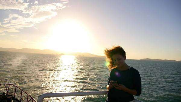 Young woman texting message while relaxing on the ship and enjoying the  sunrise  Cruise in Thailand  Andaman Sea  Slow motion  stock footage