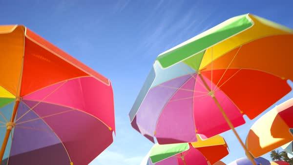 a9bd1f0acff9 Multi colored, rainbow beach umbrellas or parasols against blue sky - Stock  Video Footage - Dissolve