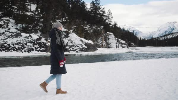 Wide-angle shot of a young woman walking along a river Royalty-free stock video
