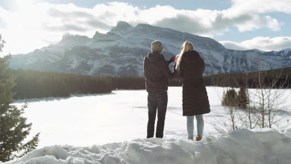 Wide-angle shot of a couple looking at mountains with binoculars Royalty-free stock video