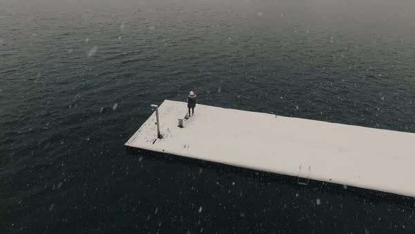Aerial of woman on a dock in a winter storm Royalty-free stock video