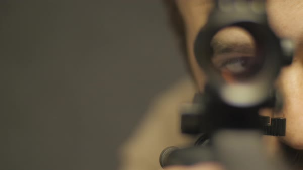 Cinematic shot of a man looking through the scope of an assault rifle from  the vantage point of the barrel of the gun  stock footage