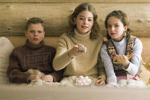 Three young siblings watching TV, teen girl changing ...