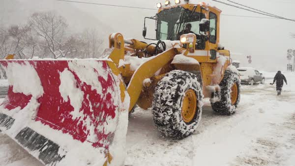 Slow motion of a tractor with a snowplow cleaning a road Royalty-free stock video