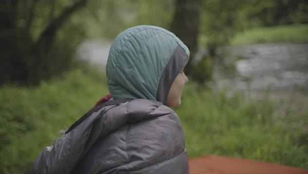 Hand-held shot of a young woman sitting up in a sleeping bag with a hood Royalty-free stock video