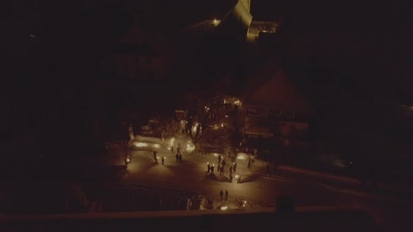 Aerial shot of people gathering on a snowy street with torches Royalty-free stock video
