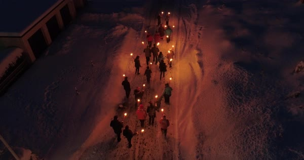 Drone shot of people walking on a snowy road with torches Royalty-free stock video