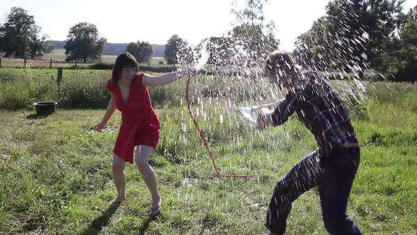 Wide shot, Handheld, couple spraying each other with water Royalty-free stock video
