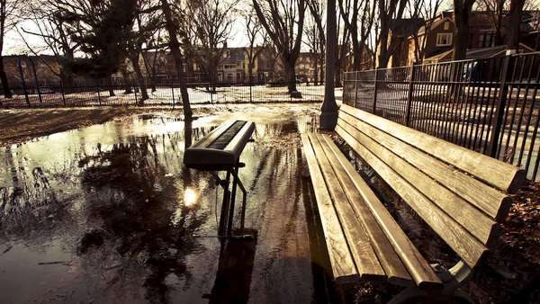 Motion timelapse of a music keyboard sitting in an icy water puddle next into a bench in a park on a sunny winter day Royalty-free stock video