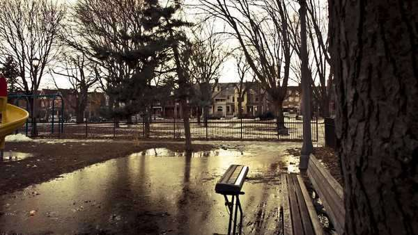 Motion timelapse revealing a music keyboard sitting in an icy water puddle next into a bench in a park on a sunny winter day Royalty-free stock video