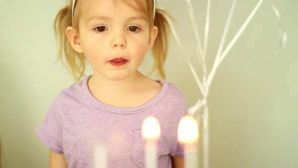 Little girl tries to blow the candles on her birthday cake Royalty-free stock video