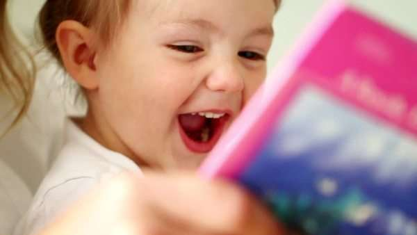 Toddler laughs as father reads book to daughters Royalty-free stock video