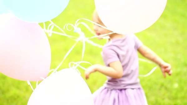 Little girl running through field with balloons Royalty-free stock video