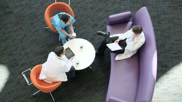 Male and female doctors sitting on chairs in a hospital in a meeting, view from above. Royalty-free stock video