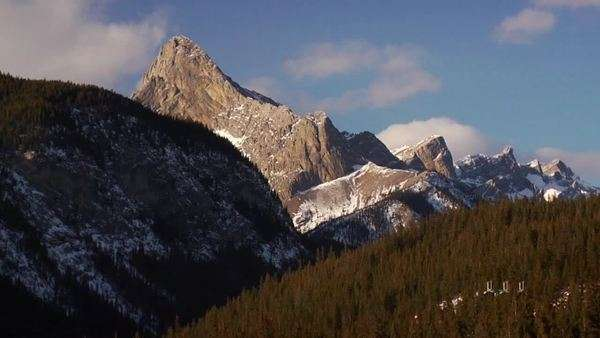 A majestic mountain alongside a smaller  mountain covered in trees Royalty-free stock video