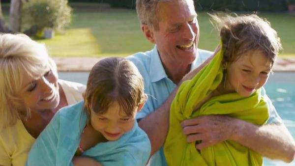 Grandparents drying grandchildren with towels by pool in garden. Royalty-free stock video