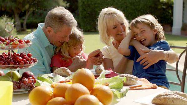 Grandparents and grandchildren playing and sitting at table of food in garden. Royalty-free stock video