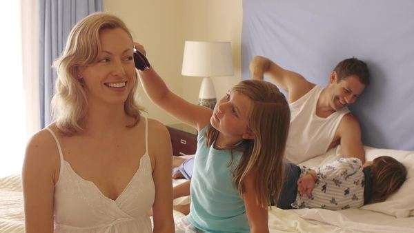 Girl brushing her mother's hair in bedroom. Royalty-free stock video